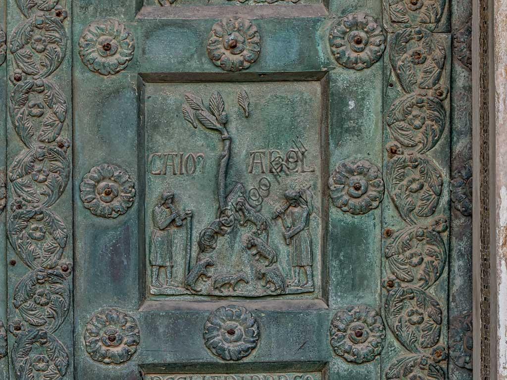 """Duomo di Monreale, Porta di Bonanno Pisano (1185-6): formella bronzea con """"Caino e Abele"""" (scena dall'Antico Testamento).La porta è firmata: """"Bonanno civis pisanus"""". Iconograficamente nei cinque ordini inferiori vi sono scene del Vecchio Testamento, sette dedicate alla storia di Adamo ed Eva, e altre sei ad altrettante coppie di profeti mentre nei cinque superiori scene del Nuovo, al sommo Cristo e Maria nella gloria del Paradiso."""