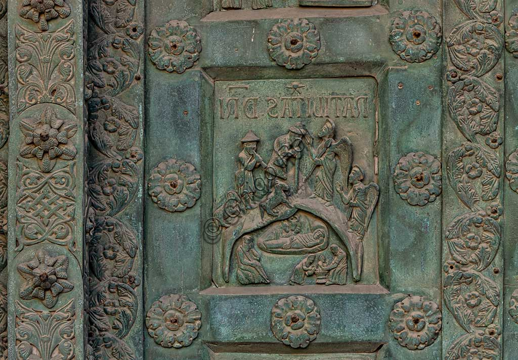 """Monreale Cathedral, the gate by Bonanno Pisano (1185-6): bronze tile depicting """"Jesus' Nativity"""" (scene of the New Testament).The gate is signed """"Bonanno civis pisanus"""". It depicts five scenes of the Old Testament at the bottom, starting with Adam and Eve, and five scenes of the New Testament at the top, ending in """"Christ and Mary in the glory of Paradise""""."""