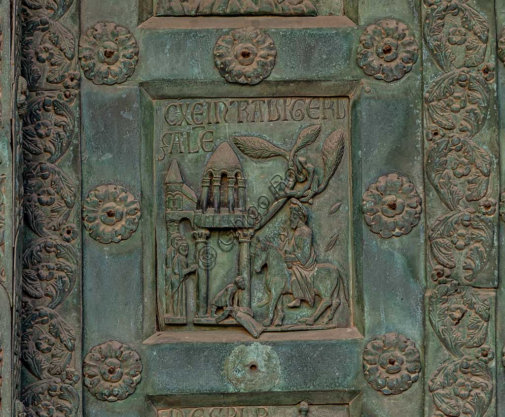 """Monreale Cathedral, the gate by Bonanno Pisano (1185-6): bronze tile depicting """"The Entrance into Jerusalem"""" (scene of the New Testament).The gate is signed """"Bonanno civis pisanus"""". It depicts five scenes of the Old Testament at the bottom, starting with Adam and Eve, and five scenes of the New Testament at the top, ending in """"Christ and Mary in the glory of Paradise""""."""