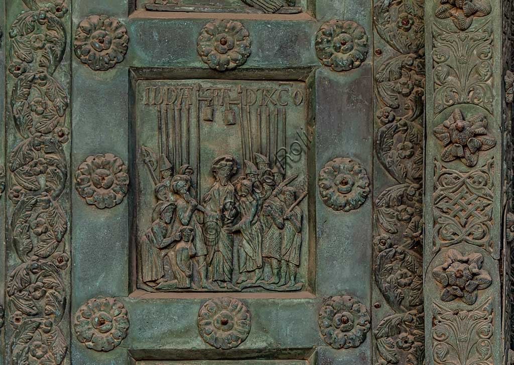 """Monreale Cathedral, the gate by Bonanno Pisano (1185-6): bronze tile depicting """"The Kiss of Judas"""" (scene of the New Testament).The gate is signed """"Bonanno civis pisanus"""". It depicts five scenes of the Old Testament at the bottom, starting with Adam and Eve, and five scenes of the New Testament at the top, ending in """"Christ and Mary in the glory of Paradise""""."""