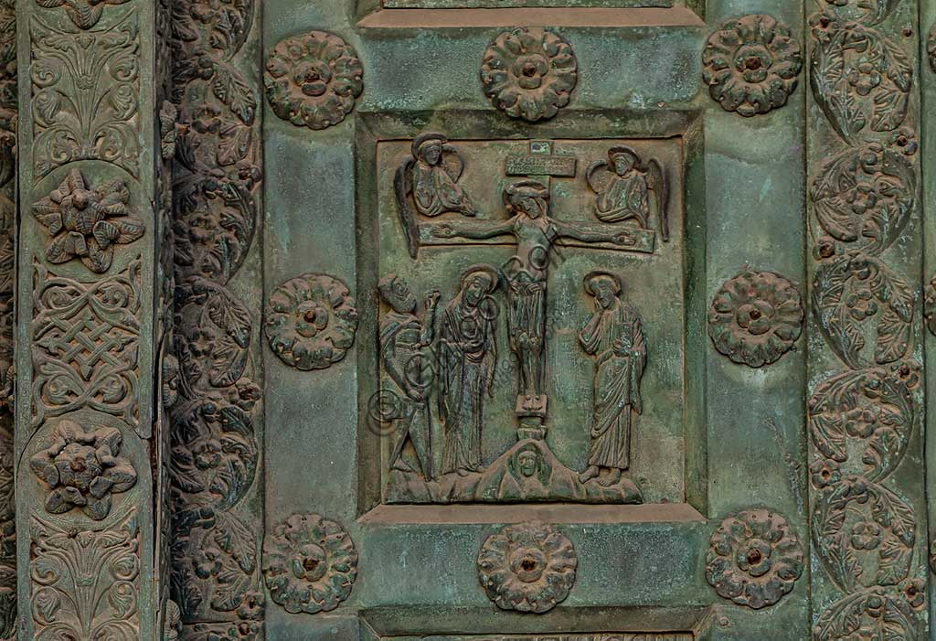 """Monreale Cathedral, the gate by Bonanno Pisano (1185-6): bronze tile depicting """"Crucifixion"""" (scene of the New Testament).The gate is signed """"Bonanno civis pisanus"""". It depicts five scenes of the Old Testament at the bottom, starting with Adam and Eve, and five scenes of the New Testament at the top, ending in """"Christ and Mary in the glory of Paradise""""."""