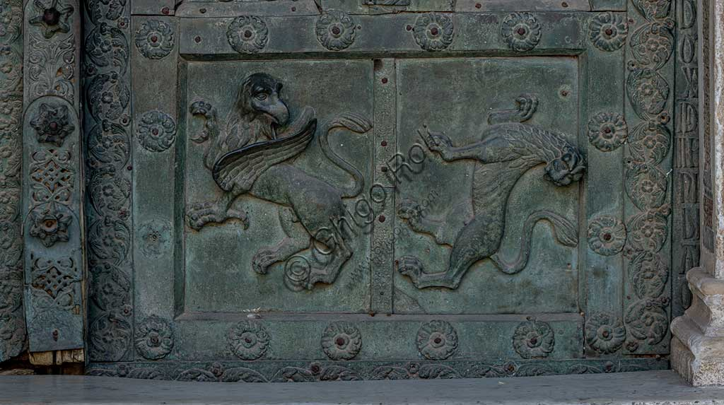 """Monreale Cathedral, the gate by Bonanno Pisano (1185-6): bronze tile depicting a grifo and a lion. The gate is signed """"Bonanno civis pisanus"""". It depicts five scenes of the Old Testament at the bottom, starting with Adam and Eve, and five scenes of the New Testament at the top, ending in """"Christ and Mary in the glory of Paradise""""."""