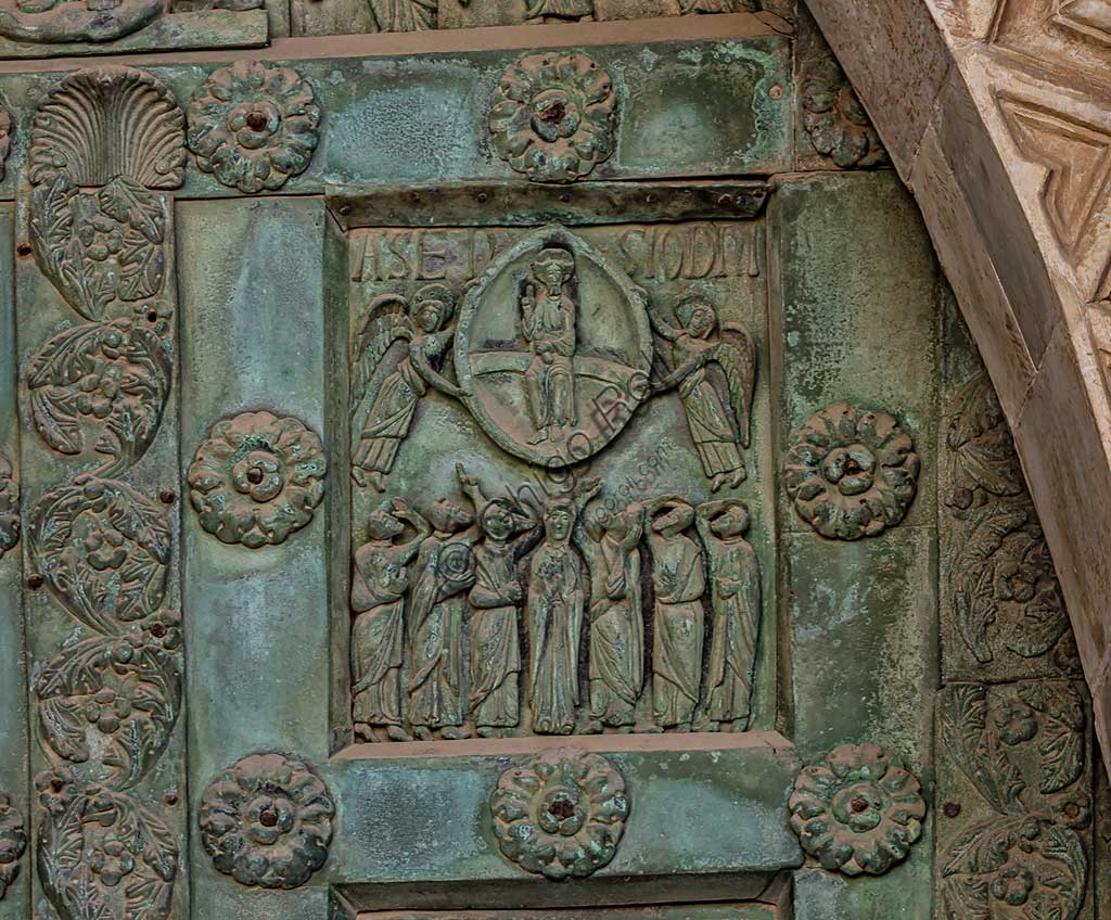 """Monreale Cathedral, the gate by Bonanno Pisano (1185-6): bronze tile depicting """"Christ's Ascension"""" (scene of the New Testament).The gate is signed """"Bonanno civis pisanus"""". It depicts five scenes of the Old Testament at the bottom, starting with Adam and Eve, and five scenes of the New Testament at the top, ending in """"Christ and Mary in the glory of Paradise""""."""