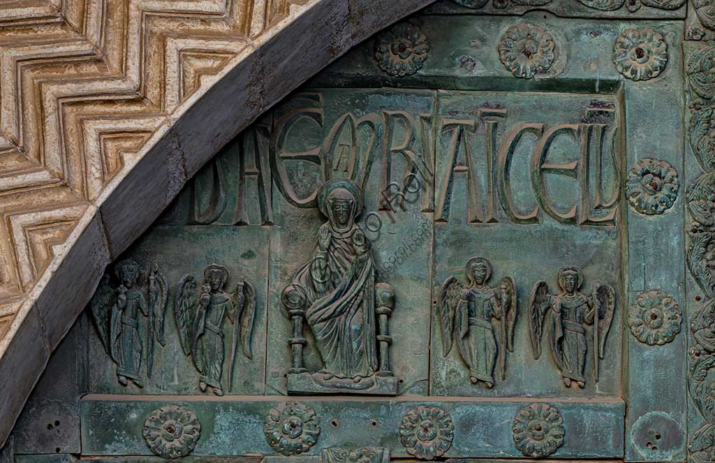 """Monreale Cathedral, the gate by Bonanno Pisano (1185-6): bronze tile depicting """"Enthroned Madonna"""" (scene of the New Testament).The gate is signed """"Bonanno civis pisanus"""". It depicts five scenes of the Old Testament at the bottom, starting with Adam and Eve, and five scenes of the New Testament at the top, ending in """"Christ and Mary in the glory of Paradise""""."""