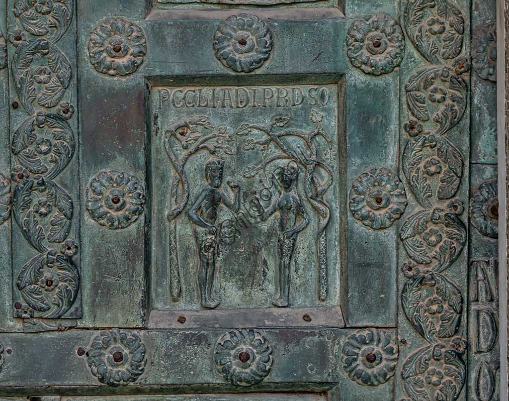 """Monreale Cathedral, the gate by Bonanno Pisano (1185-6): bronze tile depicting """"The Original Sin"""" (scene of the Old Testament).The gate is signed """"Bonanno civis pisanus"""". It depicts five scenes of the Old Testament at the bottom, starting with Adam and Eve, and five scenes of the New Testament at the top, ending in """"Christ and Mary in the glory of Paradise""""."""